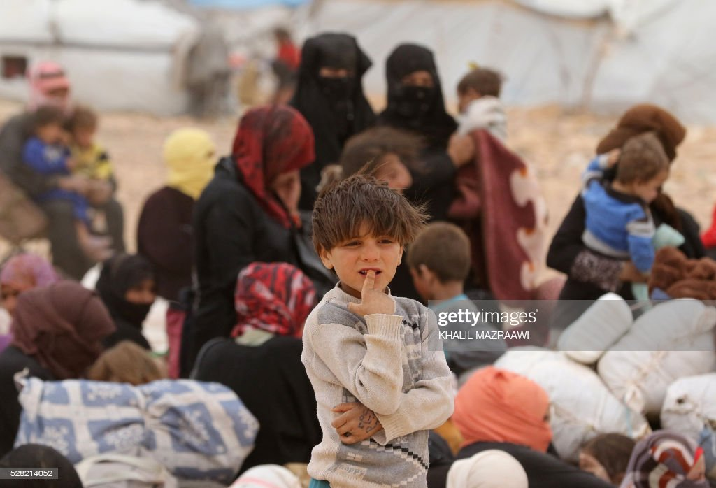 Syrian refugees wait to cross to the Jordanian side of the Hadalat border crossing, a military zone east of the capital Amman, after arriving from Syria on May 4, 2016. According to the Jordanian Commander of the Border Guards Brigadier Saber Al-Mahayreh, around 5000 Syrians fleeing from recent attacks on the northern Syrian city of Aleppo are trying to cross into Jordan in search of safety, most of whom are exhausted and desperately in need of help and medical treatment. MAZRAAWI