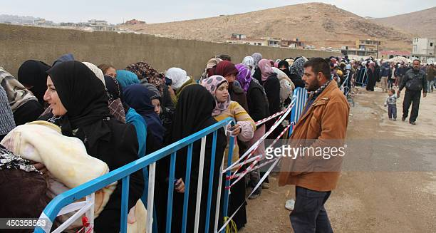 Syrian refugees wait to register upon their arrival in the strategic Lebanese border district town of Arsal on November 18 after fleeing the fighting...