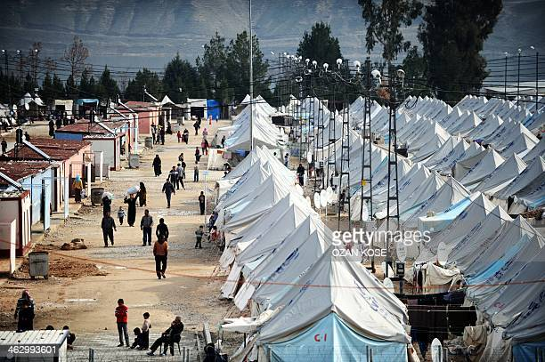 Syrian refugees walk among tents at Karkamis' refugee camp on January 16 2014 near the town of Gaziantep south of Turkey Two weeks of battles between...
