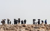 Syrian refugees walk near the Syrian town of Tal Abyad at Akcakale in Sanliurfa province on June 12 2015 Turkey said it was taking measures to limit...