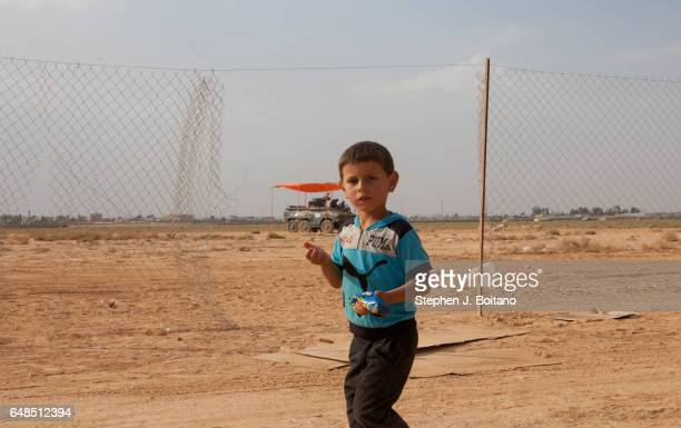 Syrian refugees walk past huge holes in the fence in the Zaatari Refugee Camp Jordan Huge areas of the fence are down making it easy to escape the...
