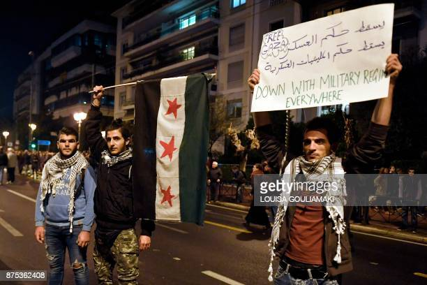 Syrian refugees wave the Syrian national flag and carry a sign as students march in front of the US embassy in Athens commemorating the 1973 Athens...