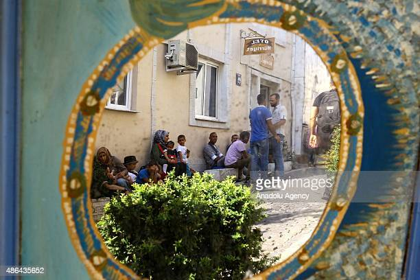 Syrian refugees who escaped from Syria with their families are seen at the entrance of a hostel in Izmir Turkey on September 4 2015 Syrians who came...
