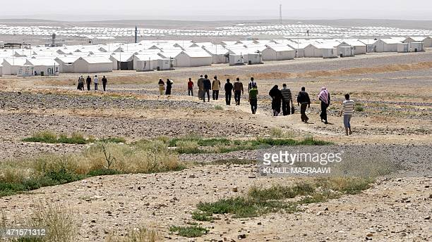TAHA Syrian refugees who fled the deadly conflict in their country walk towards prefabricated buildings at Azraq refugee camp on April 28 2015 in...