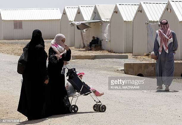 TAHA Syrian refugees who fled the deadly conflict in their country walk past prefabricated buildings at Azraq refugee camp on April 28 2015 in Jordan...