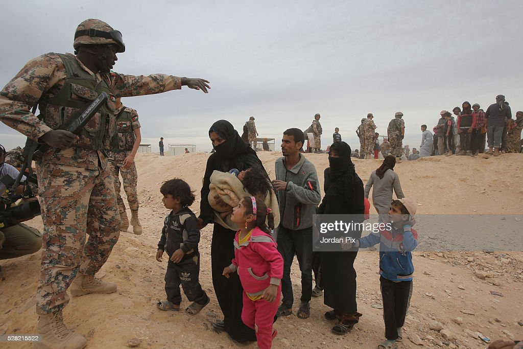 Syrian refugees who have arrived at the Jordanian military crossing point of Hadalat at the border with Syria are allowed to cross to Jordan after a long walk through the Syrian desert on May 4, 2016 in Hadalat, Jordan. Coming from the cities of Raqaa, Deir Al-Zor and Hama, roughly 300 hundred refugees crossed into Jordan at Hadalat on Wednesday, while over 5000 refugees crossed in the last four days coming from Aleppo.