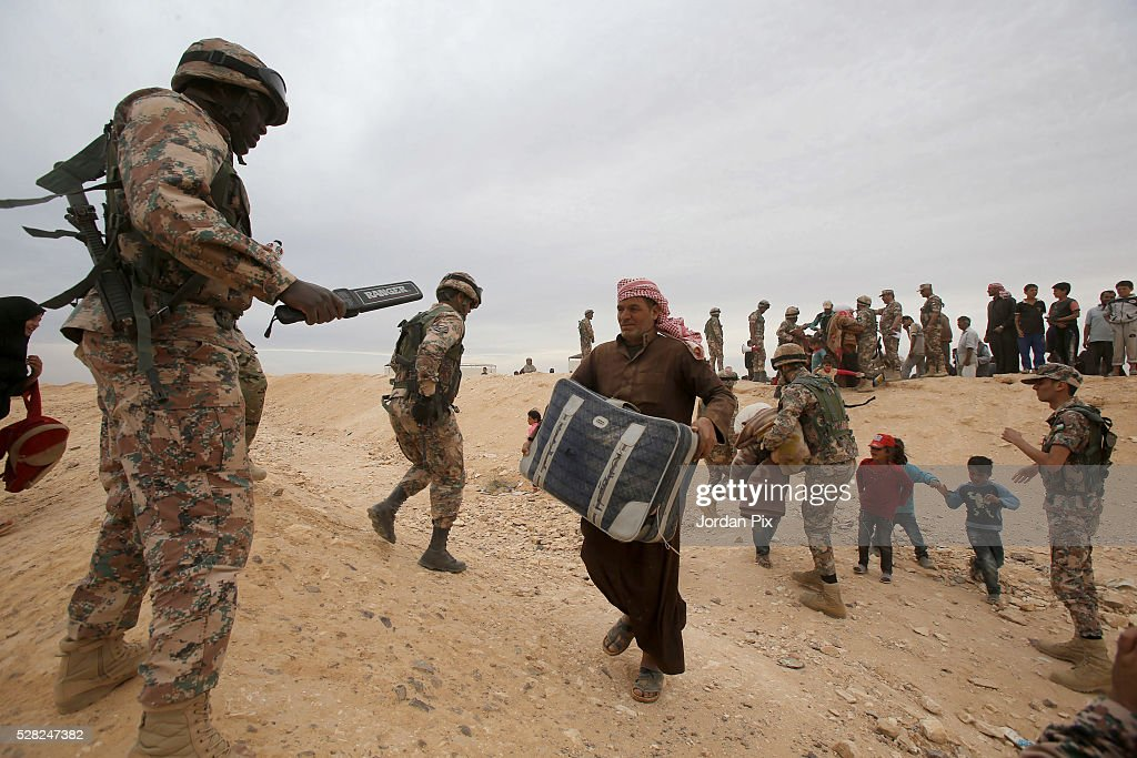Syrian refugees who have arrived at the Jordanian military crossing point of Hadalat at the border with Syria are checked with a metal detector before crossing into Jordan after a long walk through the Syrian desert on May 4, 2016 in Hadalat, Jordan. Coming from the cities of Raqaa, Deir Al-Zor and Hama, roughly 300 hundred refugees crossed into Jordan at Hadalat on Wednesday, while over 5000 refugees crossed in the last four days coming from Aleppo.