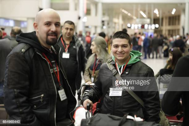 Syrian refugees who were granted humanitarian visas by the Italian government pose for a picture as they wait at the departures hall in Beirut's...