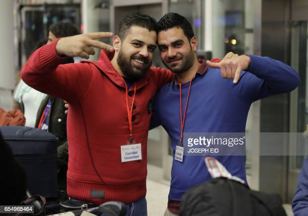 Syrian refugees who were granted humanitarian visas by the Italian government pose for a picture as they head to the departures hall in Beirut's...