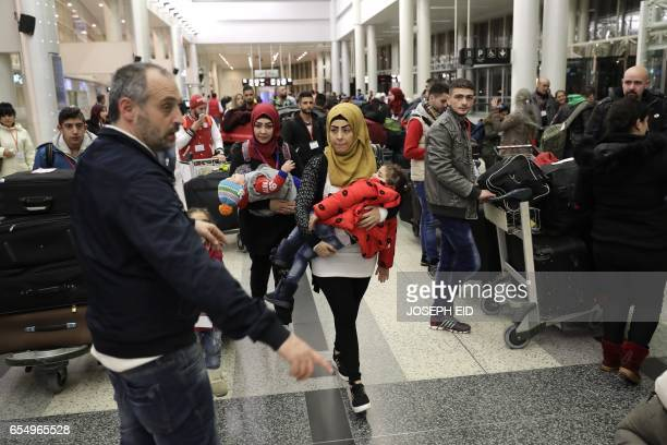 Syrian refugees who were granted humanitarian visas by the Italian government head to the departures hall in Beirut's International airport on March...