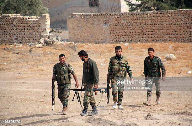 Syrian regime soldiers walk in an area in the eastern outskirts of the northern Syrian city of Aleppo on October 23 2015 Syrian government forces...