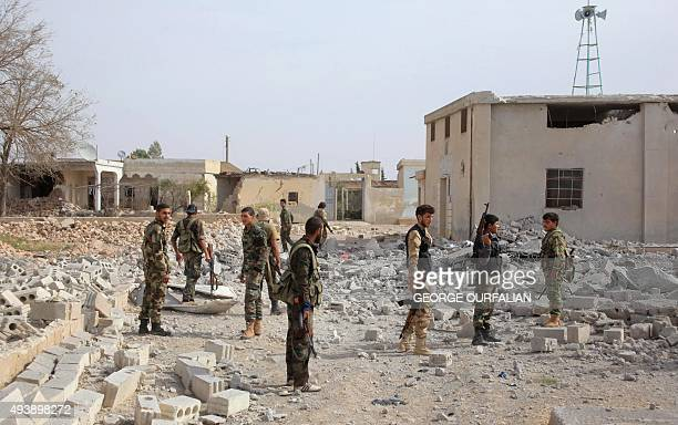Syrian regime soldiers walk near debris on the eastern outskirts of the northern Syrian city of Aleppo on October 23 2015 Syrian government forces...
