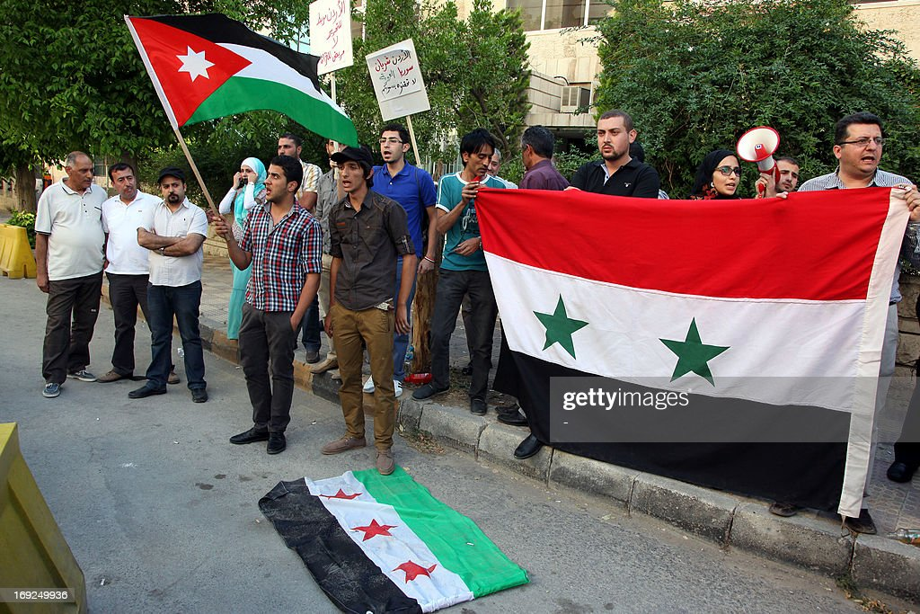 A Syrian regime supporter steps on the old Syrian flag, adopted by the rebel movement, while others hold Jordanian (L) and Syrian national flags during a protest outside Le Meridien Hotel where takes place the 'Friends of Syria' group to discuss a US-Russian proposal for peace talks on May 22, 2013 in the Jordanian capital Amman. The Damascus regime's ambassador to Jordan lashed out at the group's meeting describing it as a gathering of 'enemies of Syria'.