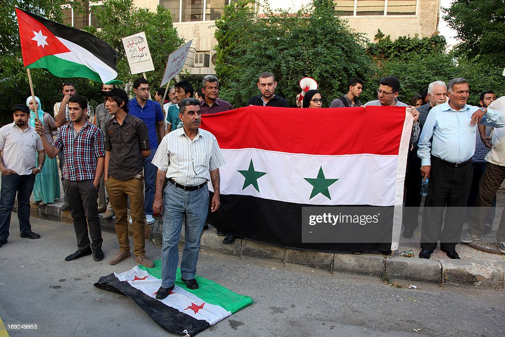 A Syrian regime supporter steps on the old Syrian flag, which was adopted by the rebel movement, while others hold Jordanian (L) and Syrian national flags during a protest outside Le Meridien Hotel where takes place the 'Friends of Syria' group to discuss a US-Russian proposal for peace talks on May 22, 2013 in the Jordanian capital Amman. The Damascus regime's ambassador to Jordan lashed out at the group's meeting describing it as a gathering of 'enemies of Syria'.
