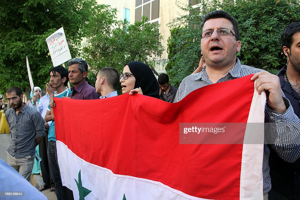 Syrian regime supporters hold a Syrian flag during a protest outside Le Meridien Hotel where takes place the 'Friends of Syria' group to discuss a US-Russian proposal for peace talks on May 22, 2013 in the Jordanian capital Amman. The Damascus regime's ambassador to Jordan lashed out at the group's meeting describing it as a gathering of 'enemies of Syria'.