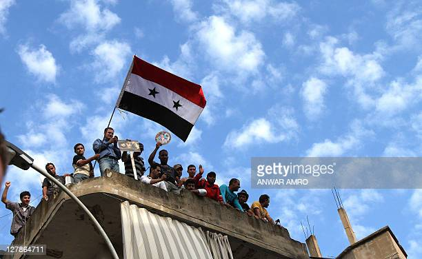 Syrian regime supporters wave the Syrian flag during a protest in the Nabaa neighborhood of Beirut on October 2 as Syrian opposition movements...