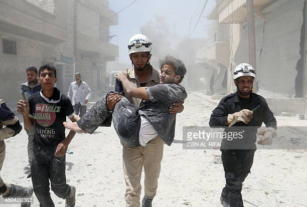 A Syrian rescue worker carries a man following an alleged airstrike by a Syrian army helicopter in the northern city of Aleppo on June 11 2014 More...