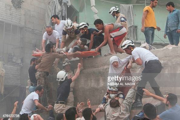 Syrian rescue workers and citizens evacuate people from a building following a reported barrel bomb attack by Syrian government forces on the central...