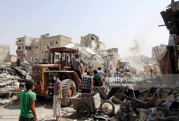 Syrian rescue workers search for survivors in the rubble of a buildings destroyed after a plane belonging to the Syrian regime forces crashed into a...