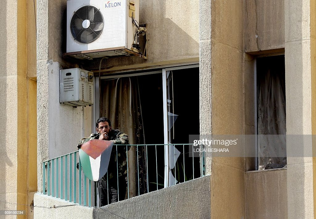 A Syrian resident watches from his balcony security forces working at the site of a suicide attack at a police officer's club in the Masaken Barzeh district of the capital Damascus on February 9, 2016. The Syrian Observatory for Human Rights said about 20 people had also been wounded, adding that policemen were among the dead and injured. BESHARA