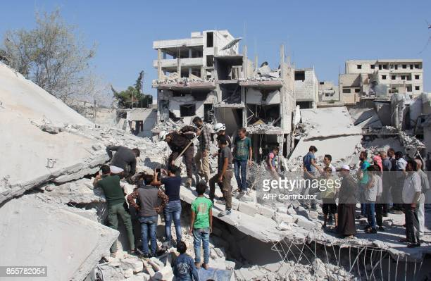 Syrian residents and members of the Syrian Civil Defence also known as White Helmets search for victims amid the rubble of a building following a...