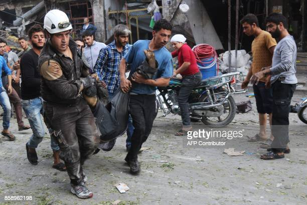 TOPSHOT Syrian residents and members of the Syrian Civil Defence also known as White Helmets carry a victim following a reported air strike on a...