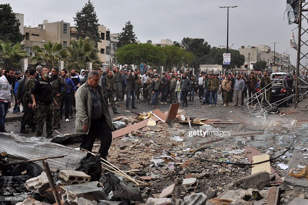 Syrian residents and security forces inspect the damage following a car bomb explosion on April 10 in the governmentcontrolled majority Alawite...