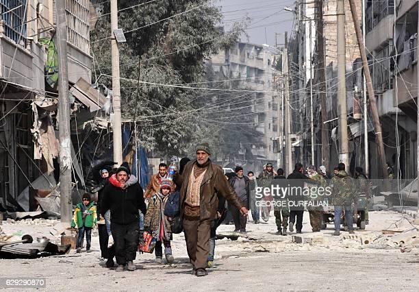 TOPSHOT Syrian residents flee violence in Aleppo's eastern alSalihin neighbourhood on December 12 2016 after regime troops retook the area from rebel...