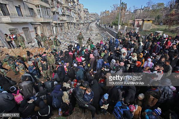 TOPSHOT Syrian residents fleeing the violence gather at a checkpoint manned by progovernment forces in the Maysaloun neighbourhood of the northern...