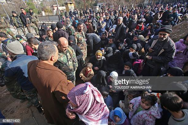 Syrian residents fleeing the violence gather at a checkpoint manned by progovernment forces in the Maysaloun neighbourhood of the northern embattled...