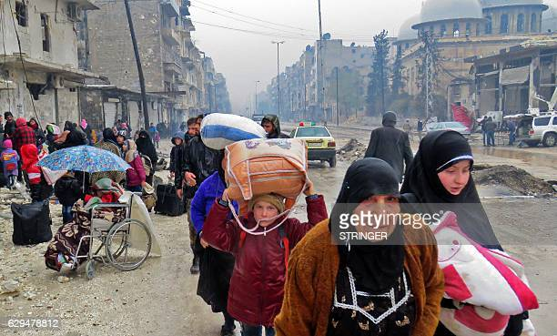 Syrian residents fleeing violence in the restive Bustan alQasr neighbourhood arrive in Aleppo's Fardos neighbourhood on December 13 after regime...