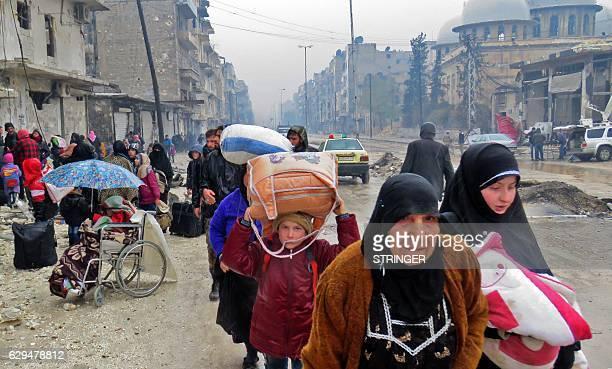 Syrian residents fleeing violence in the restive Bustan alQasr neighbourhood arrive in Aleppo's Fardos neighbourhood on December 13 after regime...
