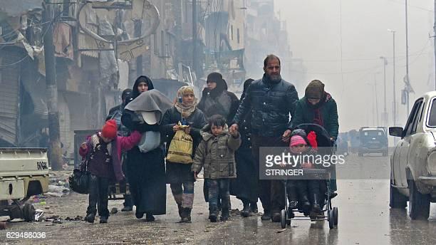 TOPSHOT Syrian residents fleeing violence in the restive Bustan alQasr neighbourhood arrive in Aleppo's Fardos neighbourhood on December 13 after...