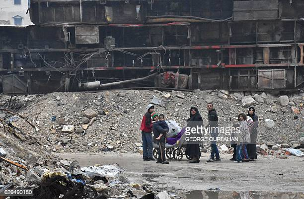 TOPSHOT Syrian residents leave Aleppo's Bustan alQasr neighbourhood after progovernment forces captured the area in the eastern part of the war torn...