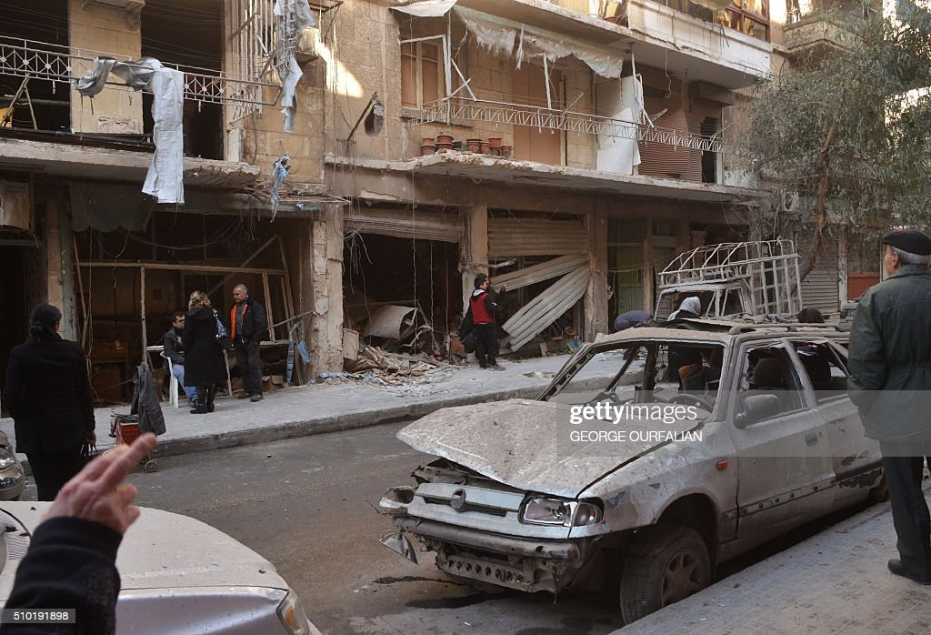 Syrian residents look at the damage following reported rebel shelling in Aleppo's government-controlled neighbourhood of Suleimaniyeh, on February 14, 2016. / AFP / GEORGE OURFALIAN