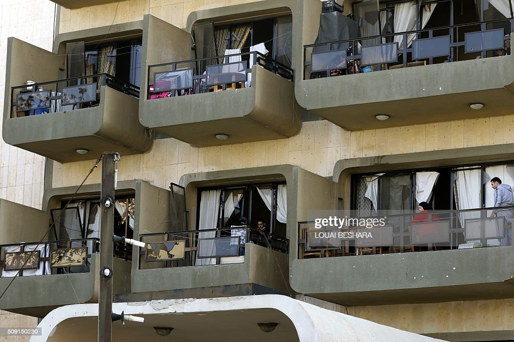 Syrian residents observe from their balconies security forces working at the site of a suicide attack at a police officer's club in the Masaken Barzeh district of the capital Damascus on February 9, 2016. The Syrian Observatory for Human Rights said about 20 people had also been wounded, adding that policemen were among the dead and injured. BESHARA