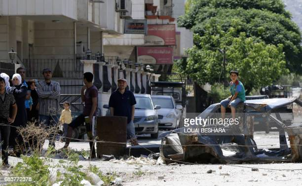 Syrian residents of the governmentheld part of the northeastern Damascus suburb of alQaboun watch by and await to receive aid shipments as regime...