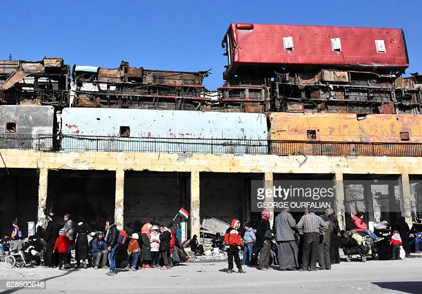 TOPSHOT Syrian residents of the newly retaken eastern neighbourhoods of Aleppo wait next to a makeshift barricade in the Bab alHadid district as they...