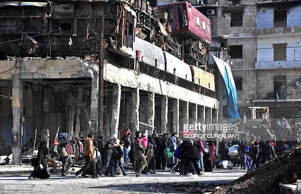 TOPSHOT Syrian residents of the newly retaken eastern neighbourhoods of Aleppo walk through the Bab alHadid district as they go back home under...