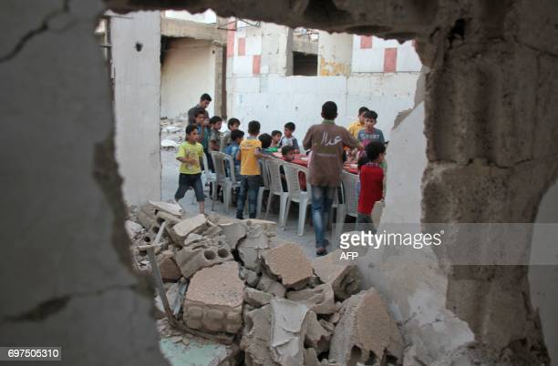 Syrian residents of the rebelheld town of Douma on the outskirts of the capital Damascus break their fast with the 'iftar' meal on a heavily damaged...