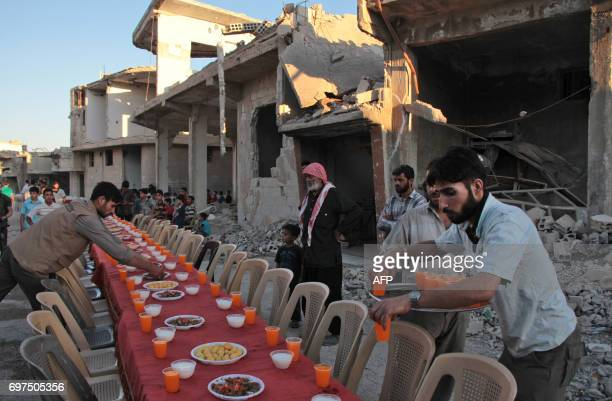 Syrian residents of the rebelheld town of Douma on the outskirts of the capital Damascus prepare to break their fast with the 'iftar' meal on a...