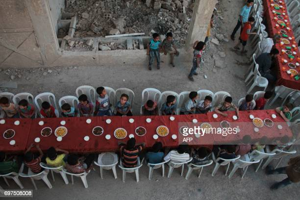 TOPSHOT Syrian residents of the rebelheld town of Douma on the outskirts of the capital Damascus break their fast with the 'iftar' meal on a heavily...