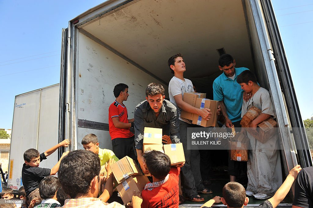 Syrian residents take goods from a truck which rebels captured at the Bab al-Hawa border crossing with Turkey on July 20, 2012, near Aleppo. Syrian rebels seized control of the Bab Al-Hawa border post with Turkey today after a fierce battle with Syrian troops, an AFP photographer at the scene reported. Some 150 armed rebel fighters were in control of the post, which lies opposite Turkey's Cilvegozu border crossing in the southern province of Hatay.