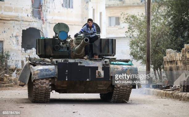 A Syrian rides on the turret of a moving tank in the rebelheld area of Daraa in southern Syria on February 4 2017 / AFP PHOTO / MOHAMAD ABAZEED