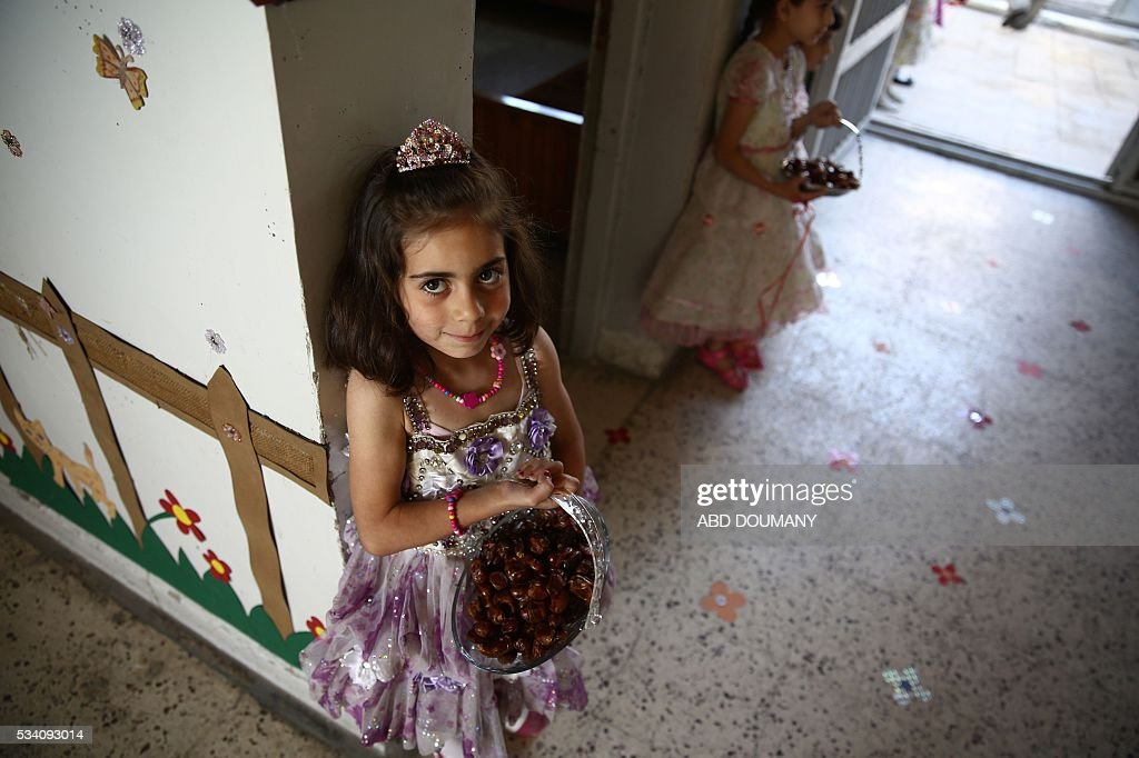 Syrian school girls carry baskets with dates at the entrance of the Saif al-Dawla school as they take part in activities surrounding an art competition organised as part of a local initiative to shift the children's minds from the atrocities of the Syrian war, on May 25, 2016, in the besieged rebel bastion of Douma, a flashpoint near the Syrian capital. / AFP / Abd Doumany