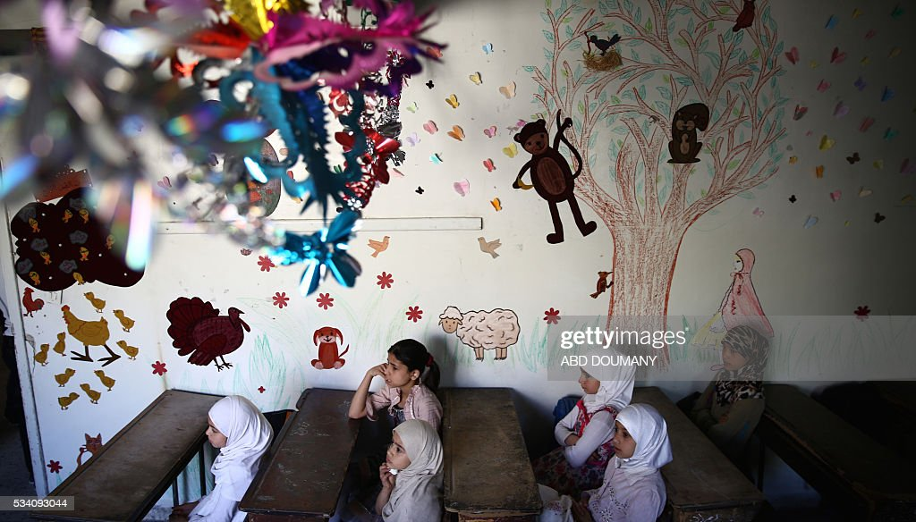 Syrian school girls sit at their classroom at the Saif al-Dawla school as they take part in activities surrounding an art competition organised as part of a local initiative to shift the children's minds from the atrocities of the Syrian war, on May 25, 2016, in the besieged rebel bastion of Douma, a flashpoint near the Syrian capital. / AFP / Abd Doumany