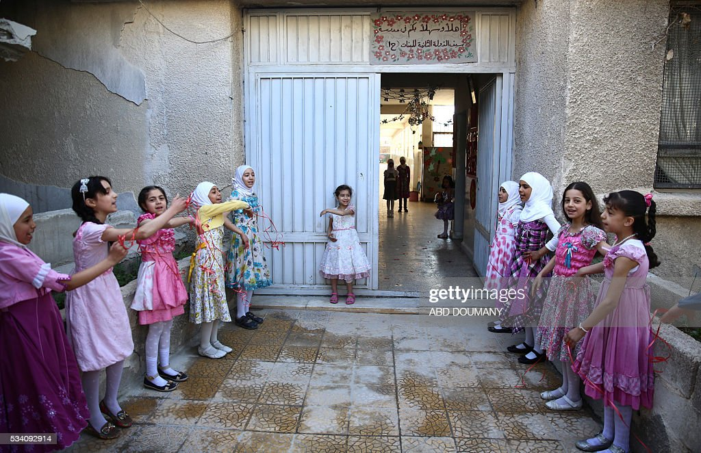 Syrian school girls stand at the entrance of the Saif al-Dawla school as they take part in activities surrounding an art competition organised as part of a local initiative to shift the children's minds from the atrocities of the Syrian war, on May 25, 2016, in the besieged rebel bastion of Douma, a flashpoint near the Syrian capital. / AFP / Abd Doumany