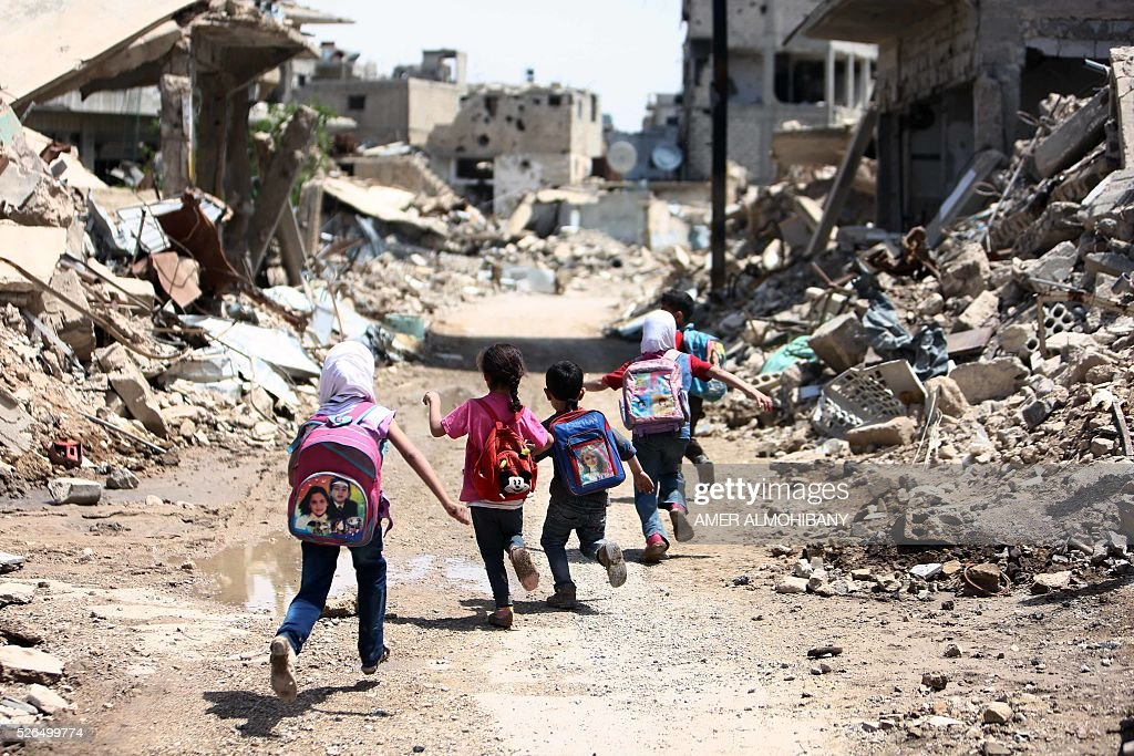 Syrian schoolchildren run past heavily damaged buildings in the rebel-held are of Jobar, on the eastern outskirts of the capital Damascus, on April 30, 2016. / AFP / AMER