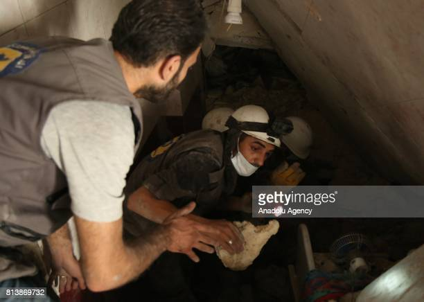 Syrian search and rescue team workers inspect a damaged building after an Assad Regime's fighter jet hit residential areas with a vacuum bomb at the...
