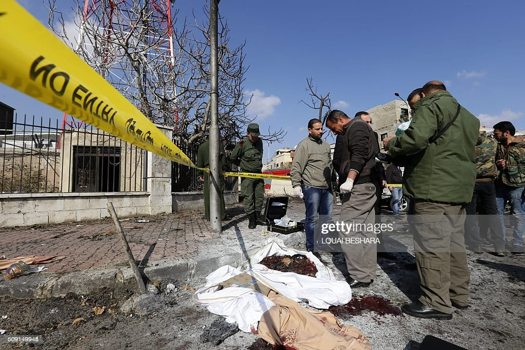Syrian security forces and policemen gather at the site of a suicide attack at a police officer's club in the Masaken Barzeh district of the capital Damascus on February 9, 2016. The Syrian Observatory for Human Rights said about 20 people had also been wounded, adding that policemen were among the dead and injured. BESHARA
